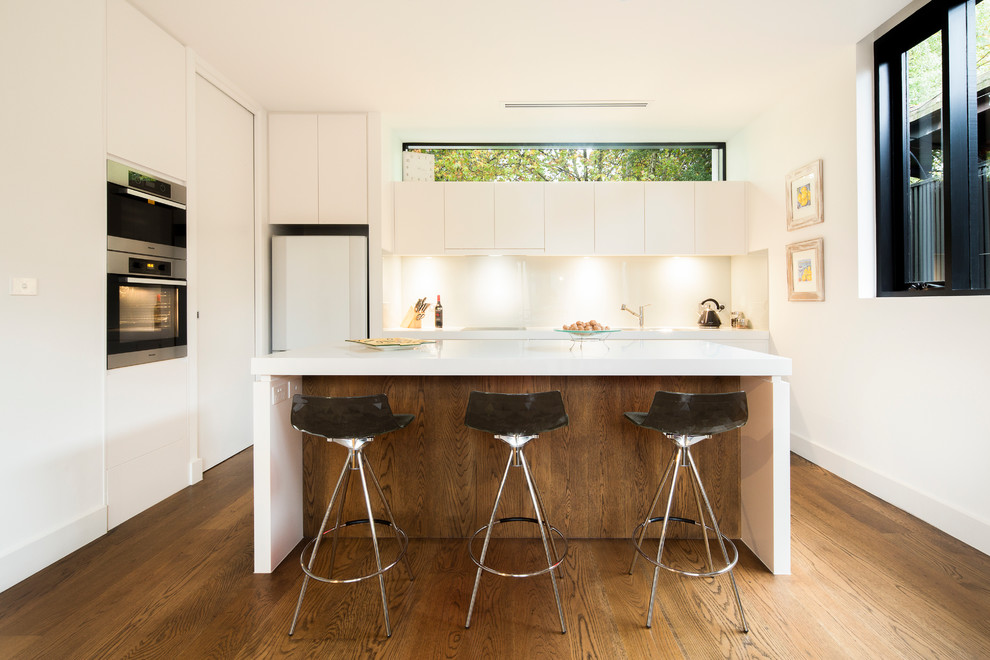Mid-sized minimalist galley medium tone wood floor kitchen photo in Melbourne with an undermount sink, flat-panel cabinets, white cabinets, quartz countertops, white backsplash, glass sheet backsplash, stainless steel appliances and an island