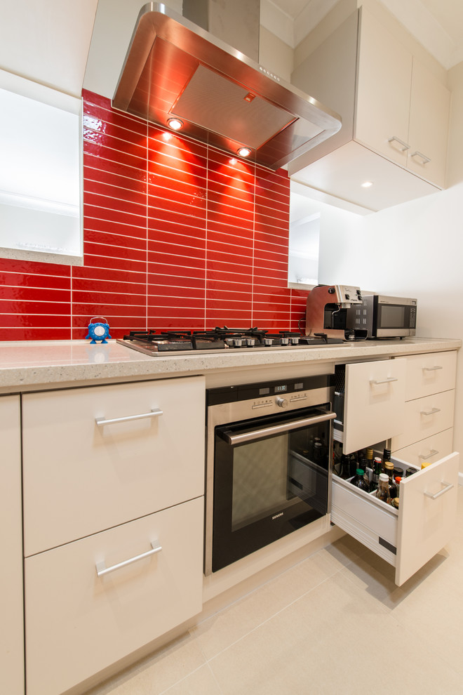 Example of a trendy kitchen design in Melbourne with flat-panel cabinets, white cabinets and red backsplash