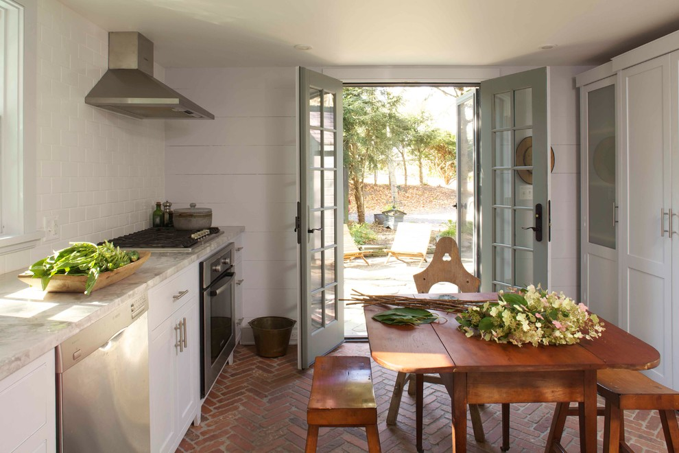 Kitchen - farmhouse brick floor kitchen idea in New York with shaker cabinets, white cabinets, marble countertops, white backsplash, subway tile backsplash and stainless steel appliances