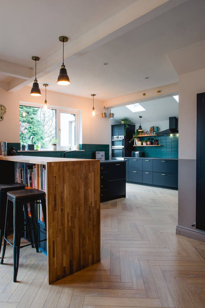 Eat-in kitchen - contemporary l-shaped light wood floor and beige floor eat-in kitchen idea in Other with flat-panel cabinets, black cabinets, wood countertops, green backsplash, subway tile backsplash, stainless steel appliances, a peninsula and brown countertops