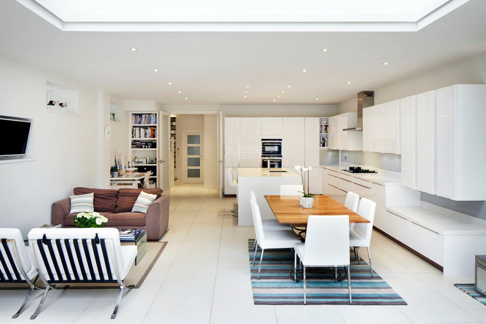 Trendy galley open concept kitchen photo in London with flat-panel cabinets, white cabinets and an island