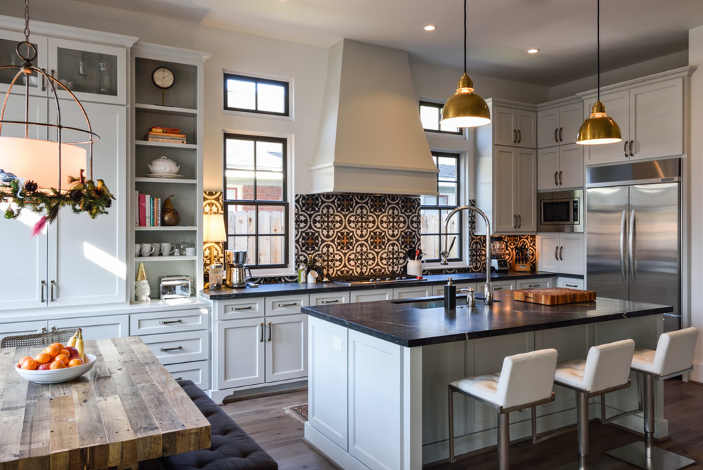 Example of a large transitional l-shaped medium tone wood floor eat-in kitchen design in Houston with an undermount sink, shaker cabinets, white cabinets, soapstone countertops, multicolored backsplash, cement tile backsplash, stainless steel appliances and an island