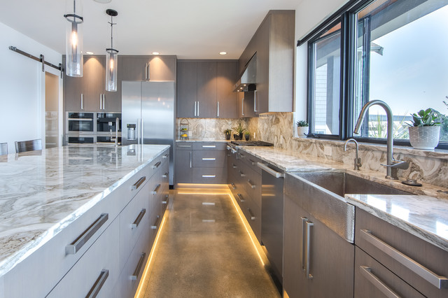 Trendy l-shaped concrete floor and gray floor kitchen photo in Seattle with a farmhouse sink, flat-panel cabinets, gray cabinets, stainless steel appliances, an island and beige countertops