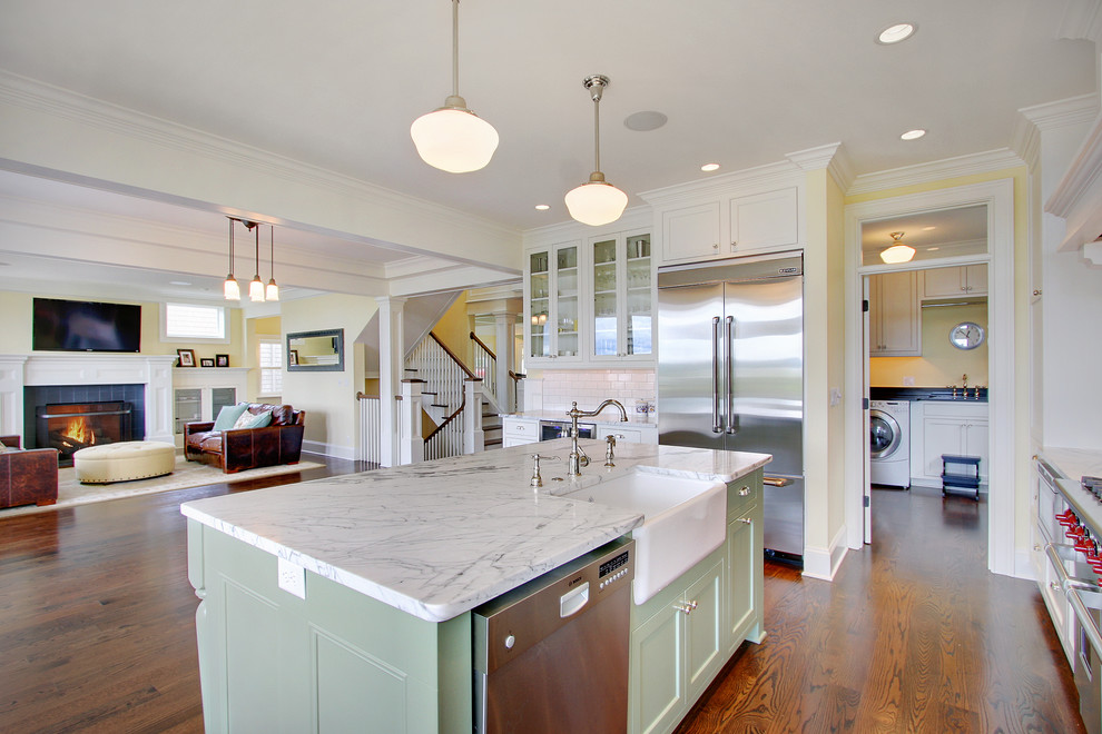 Inspiration for a timeless kitchen remodel in Seattle with glass-front cabinets, stainless steel appliances, a farmhouse sink and green cabinets