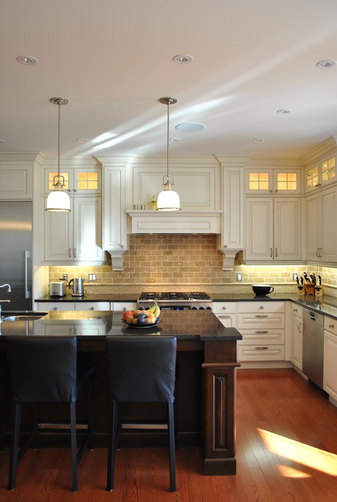 Inspiration for a timeless l-shaped kitchen remodel in Ottawa with raised-panel cabinets, stainless steel appliances, white cabinets and travertine backsplash