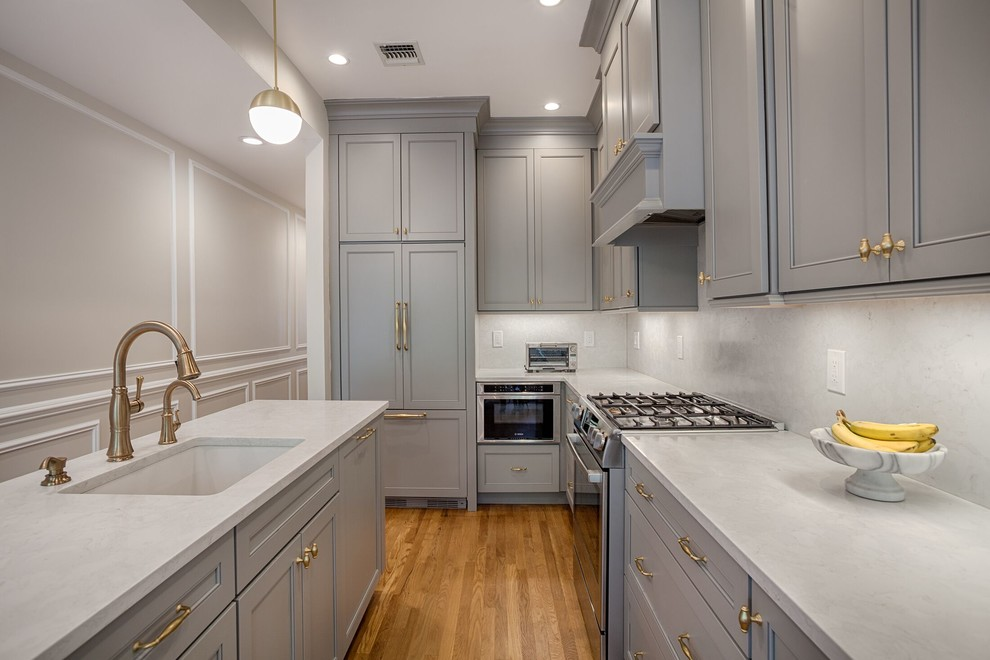 Kitchen - small transitional l-shaped medium tone wood floor and beige floor kitchen idea in New York with recessed-panel cabinets, gray cabinets, white backsplash, stainless steel appliances, an island, an undermount sink, quartzite countertops, stone slab backsplash and white countertops