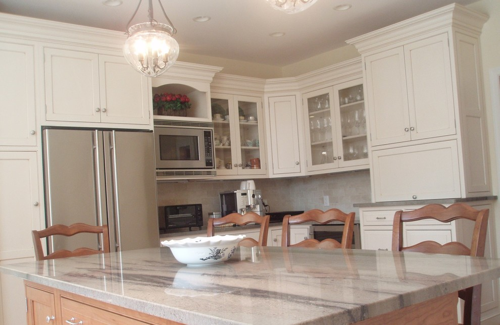 Mid-sized trendy l-shaped eat-in kitchen photo in Boston with an undermount sink, shaker cabinets, white cabinets, granite countertops, beige backsplash, ceramic backsplash, stainless steel appliances and an island