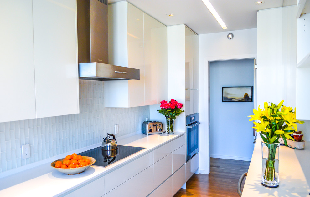 Enclosed kitchen - small modern galley light wood floor enclosed kitchen idea in Atlanta with an undermount sink, flat-panel cabinets, white cabinets, solid surface countertops, white backsplash, glass tile backsplash, stainless steel appliances and no island