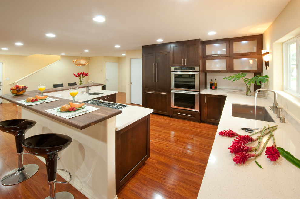 Example of a large island style l-shaped medium tone wood floor and brown floor kitchen design in Hawaii with an undermount sink, shaker cabinets, dark wood cabinets, solid surface countertops, white backsplash, paneled appliances and no island