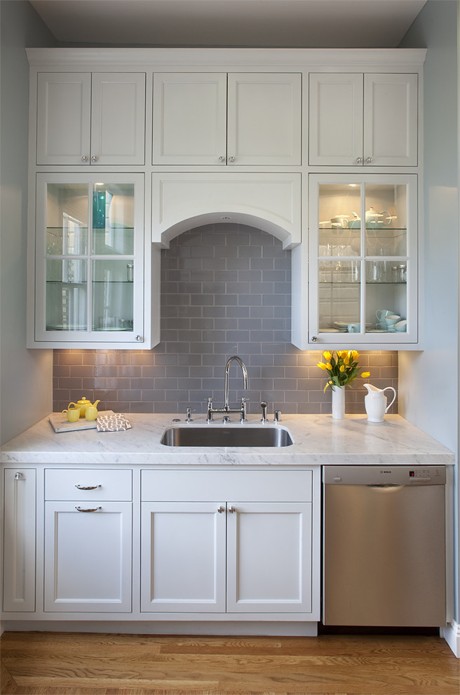Elegant kitchen photo in San Francisco with glass-front cabinets, subway tile backsplash and stainless steel appliances