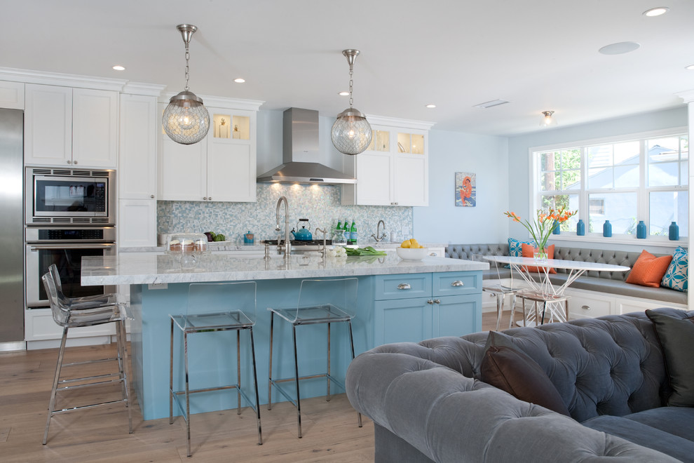 Example of a large beach style l-shaped medium tone wood floor eat-in kitchen design in Los Angeles with a farmhouse sink, shaker cabinets, white cabinets, blue backsplash, mosaic tile backsplash, stainless steel appliances, an island and marble countertops