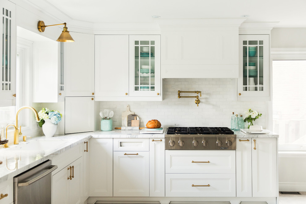 Example of a farmhouse kitchen design in Toronto with an undermount sink, beaded inset cabinets, white cabinets, white backsplash and stainless steel appliances