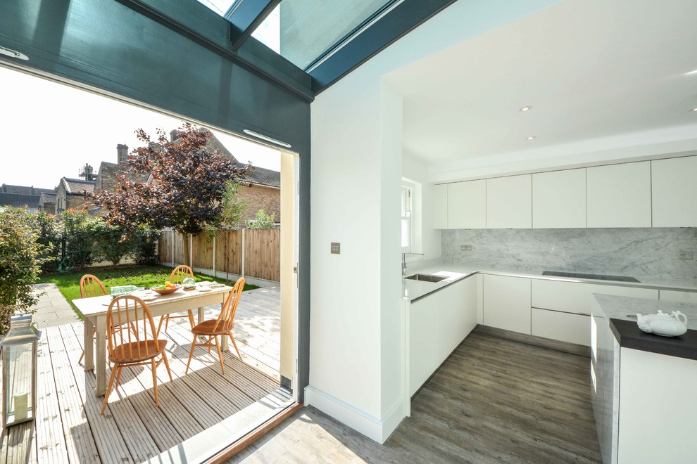 This is an example of an expansive contemporary l-shaped enclosed kitchen in Kent with a submerged sink, flat-panel cabinets, white cabinets, marble worktops, grey splashback, stone slab splashback, stainless steel appliances, lino flooring and an island.