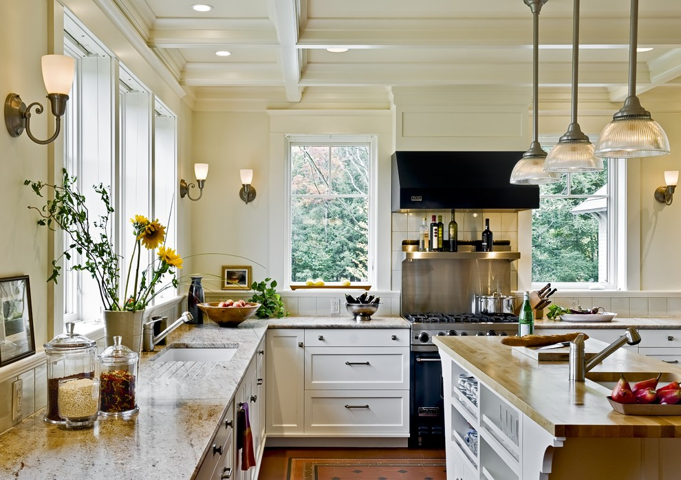 Example of a classic kitchen design in Burlington with wood countertops, an undermount sink, recessed-panel cabinets, white cabinets and black appliances