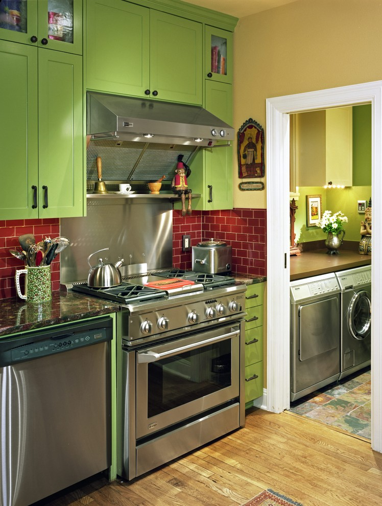 Example of a trendy kitchen design in Austin with stainless steel appliances, red backsplash, recessed-panel cabinets and green cabinets