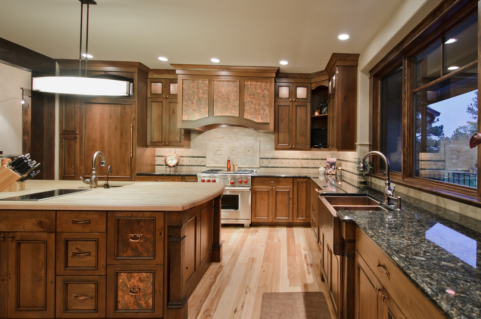 Inspiration for a rustic l-shaped kitchen remodel in Denver with paneled appliances, a double-bowl sink, wood countertops and dark wood cabinets