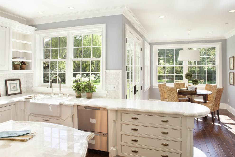 Eat-in kitchen - large traditional l-shaped medium tone wood floor eat-in kitchen idea in San Francisco with a farmhouse sink, beaded inset cabinets, white cabinets, marble countertops, white backsplash, mosaic tile backsplash, stainless steel appliances and an island