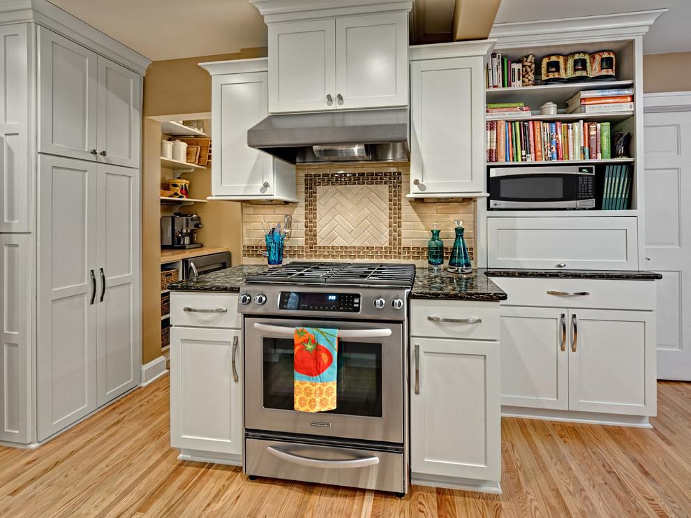 Elegant kitchen photo in Minneapolis with shaker cabinets, white cabinets, brown backsplash, subway tile backsplash and stainless steel appliances