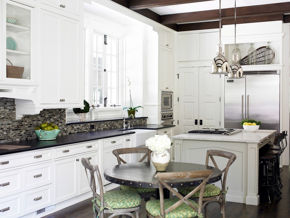 Mid-sized transitional l-shaped dark wood floor eat-in kitchen photo in Atlanta with stainless steel appliances, a farmhouse sink, white cabinets, black backsplash, glass tile backsplash, granite countertops, shaker cabinets and an island