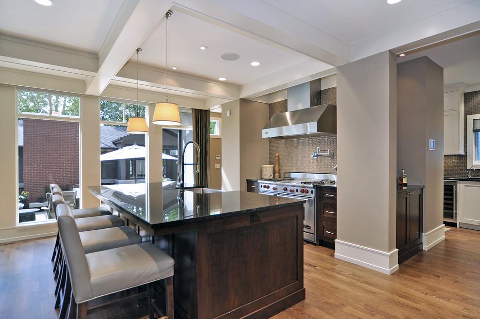 Transitional light wood floor kitchen photo in Calgary with stainless steel appliances, dark wood cabinets, granite countertops, metallic backsplash and mosaic tile backsplash