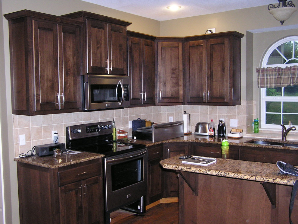 Example of a mid-sized classic l-shaped medium tone wood floor and brown floor kitchen design in Kansas City with a double-bowl sink, raised-panel cabinets, dark wood cabinets, granite countertops, beige backsplash, ceramic backsplash, stainless steel appliances and an island