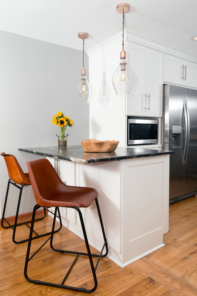 Inspiration for a mid-sized transitional u-shaped medium tone wood floor and beige floor eat-in kitchen remodel in Other with a farmhouse sink, shaker cabinets, gray cabinets, marble countertops, multicolored backsplash, stone tile backsplash, stainless steel appliances, a peninsula and black countertops