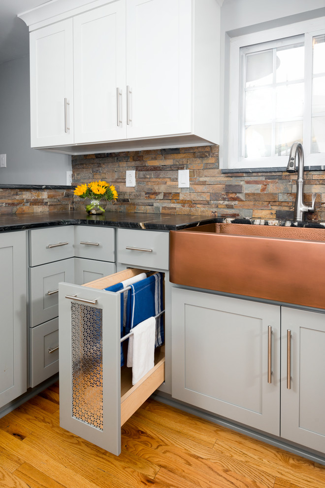 Eat-in kitchen - mid-sized transitional u-shaped medium tone wood floor and beige floor eat-in kitchen idea in Other with a farmhouse sink, shaker cabinets, gray cabinets, marble countertops, multicolored backsplash, stone tile backsplash, stainless steel appliances, a peninsula and black countertops