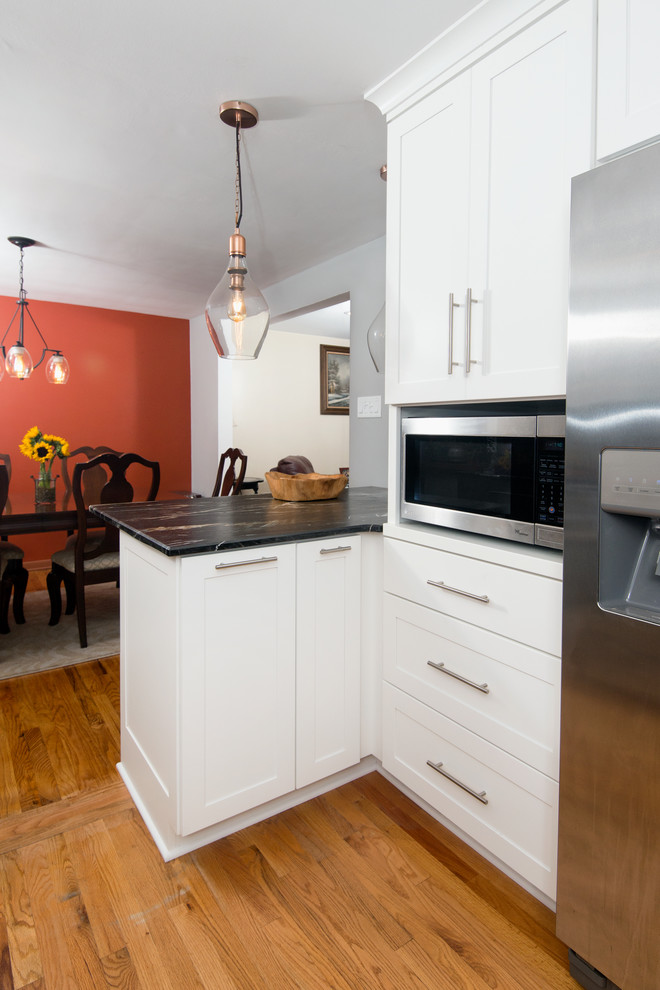 Mid-sized transitional u-shaped medium tone wood floor and beige floor eat-in kitchen photo in Other with a farmhouse sink, shaker cabinets, gray cabinets, marble countertops, multicolored backsplash, stone tile backsplash, stainless steel appliances, a peninsula and black countertops