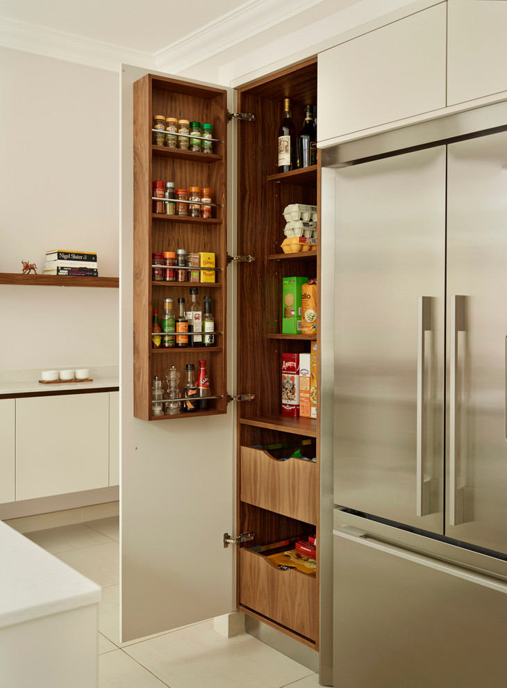 Example of a large trendy kitchen pantry design in London with flat-panel cabinets, white cabinets and stainless steel appliances