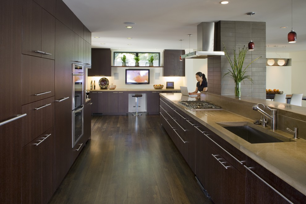 Trendy eat-in kitchen photo in San Francisco with stainless steel appliances, an undermount sink, flat-panel cabinets, dark wood cabinets and concrete countertops