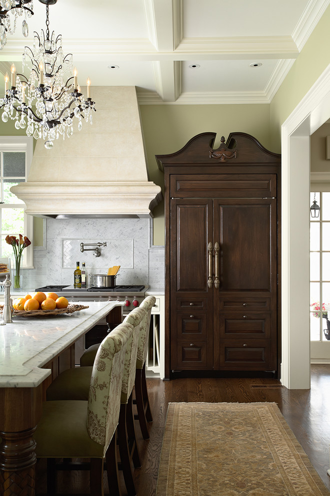 Example of a classic kitchen design in Minneapolis with raised-panel cabinets, dark wood cabinets, marble countertops, white backsplash, stone tile backsplash and paneled appliances