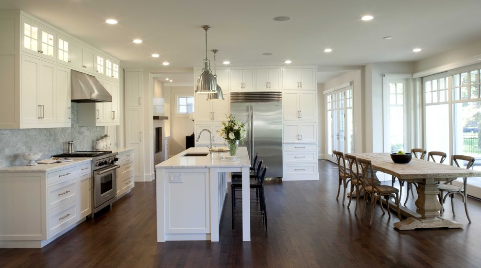 Example of a classic dark wood floor eat-in kitchen design in Minneapolis with stainless steel appliances, marble countertops, white cabinets, gray backsplash, stone tile backsplash, an undermount sink, recessed-panel cabinets and white countertops