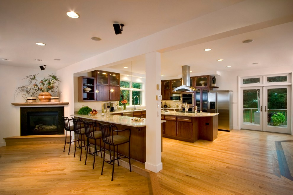 Eat-in kitchen - large transitional u-shaped medium tone wood floor eat-in kitchen idea in Other with a double-bowl sink, dark wood cabinets, granite countertops, stainless steel appliances and an island