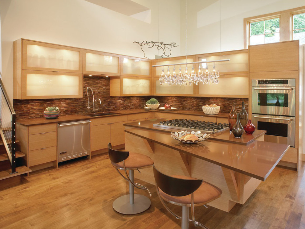 Large trendy l-shaped light wood floor and beige floor open concept kitchen photo in New York with an undermount sink, light wood cabinets, quartz countertops, stainless steel appliances, an island, glass-front cabinets and brown countertops