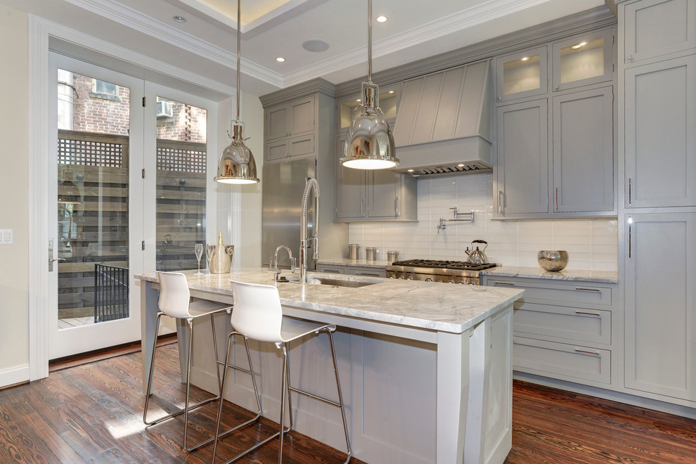 Example of a classic galley dark wood floor kitchen design in DC Metro with an undermount sink, gray cabinets, quartzite countertops, glass tile backsplash, shaker cabinets, white backsplash, stainless steel appliances and an island