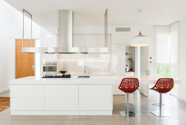 Photo of a contemporary galley kitchen in Adelaide with a double-bowl sink, flat-panel cabinets, white cabinets, white splashback, stainless steel appliances, concrete flooring and an island.