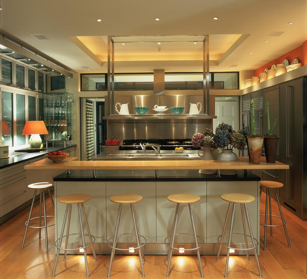 Trendy u-shaped medium tone wood floor kitchen photo in London with flat-panel cabinets, gray cabinets, metallic backsplash and an island