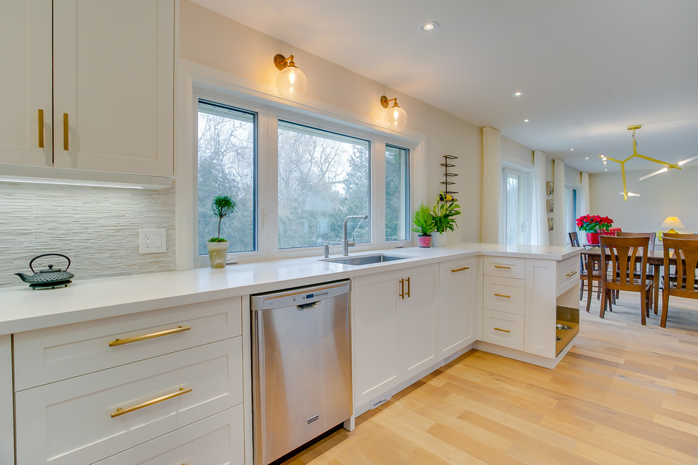 Example of a mid-sized transitional u-shaped vinyl floor eat-in kitchen design in Toronto with an undermount sink, shaker cabinets, white cabinets, zinc countertops, gray backsplash, porcelain backsplash, stainless steel appliances and white countertops