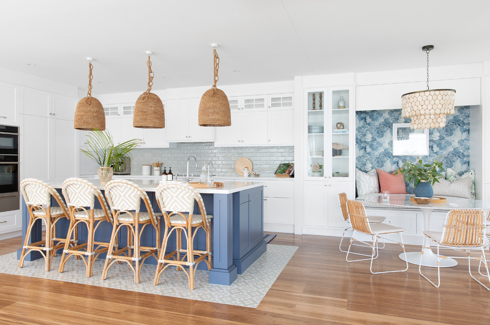 Example of a large beach style l-shaped porcelain tile and beige floor eat-in kitchen design in Gold Coast - Tweed with shaker cabinets, white cabinets, an island, white countertops, a single-bowl sink, quartz countertops, green backsplash, porcelain backsplash and stainless steel appliances
