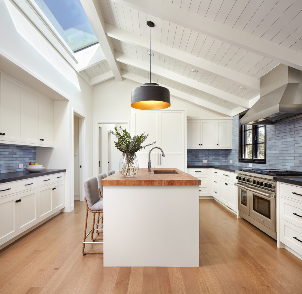 Inspiration for a transitional u-shaped medium tone wood floor, brown floor and shiplap ceiling enclosed kitchen remodel in San Francisco with an undermount sink, shaker cabinets, white cabinets, wood countertops, blue backsplash, subway tile backsplash, paneled appliances, an island and brown countertops