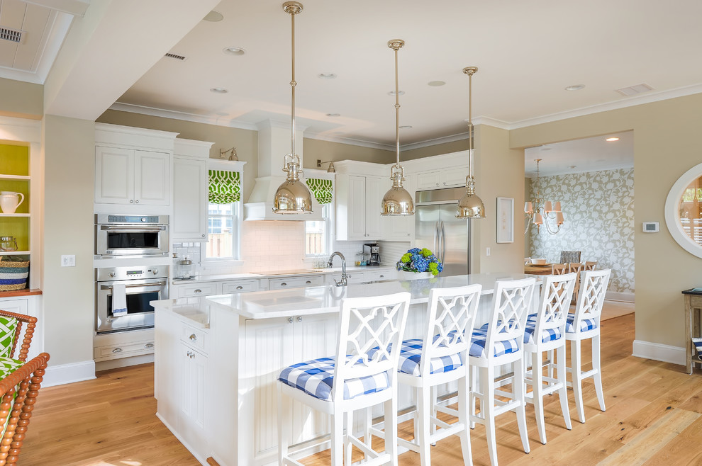 Inspiration for a mid-sized coastal light wood floor open concept kitchen remodel in Philadelphia with recessed-panel cabinets, white cabinets, quartz countertops, white backsplash, ceramic backsplash, stainless steel appliances and an island
