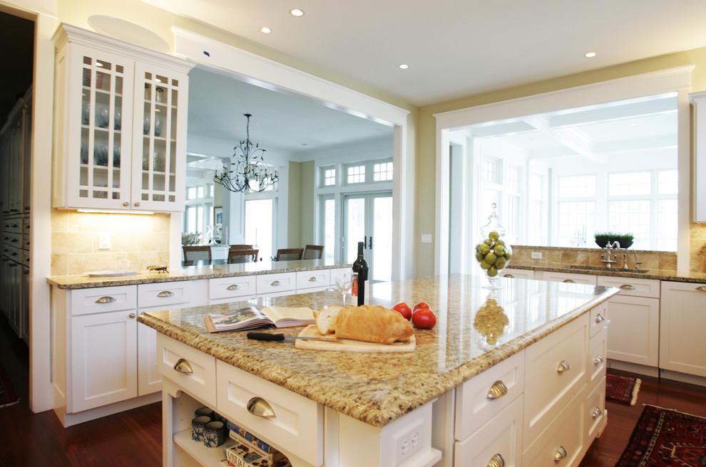 Réalisation d'une cuisine tradition avec un placard à porte vitrée, un plan de travail en granite et des portes de placard blanches.