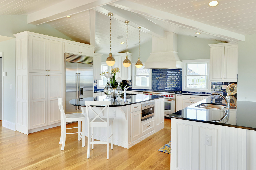 Beach style u-shaped kitchen photo in Other with stainless steel appliances, a double-bowl sink, recessed-panel cabinets, white cabinets, granite countertops, blue backsplash and subway tile backsplash