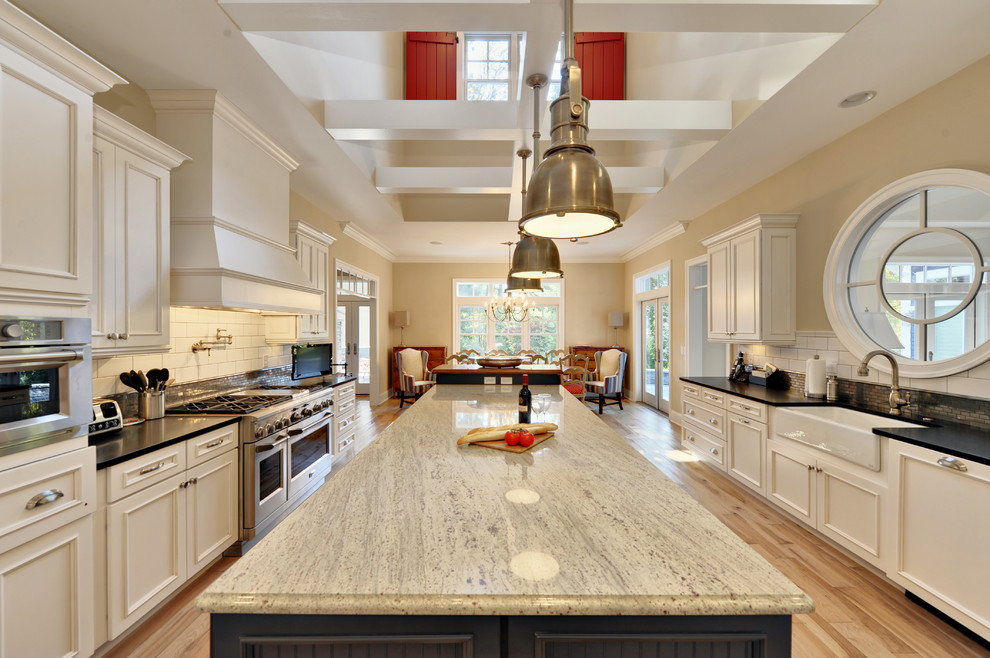 Beach style eat-in kitchen photo in Philadelphia with stainless steel appliances, subway tile backsplash, a farmhouse sink, granite countertops, recessed-panel cabinets, white cabinets, white backsplash and black countertops