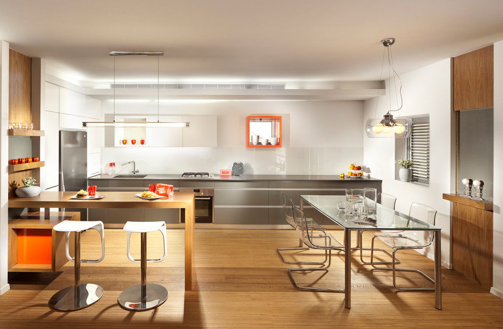 Inspiration for a modern eat-in kitchen remodel in Other with flat-panel cabinets, gray cabinets, white backsplash, glass sheet backsplash and stainless steel appliances