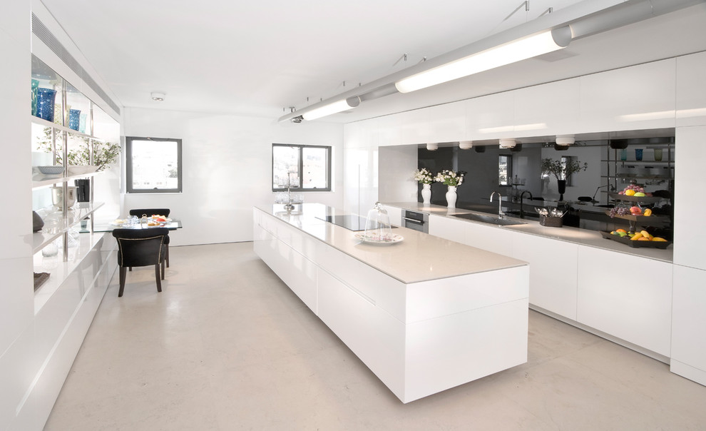 Minimalist galley kitchen photo in Other with flat-panel cabinets, white cabinets, black backsplash, glass sheet backsplash and paneled appliances