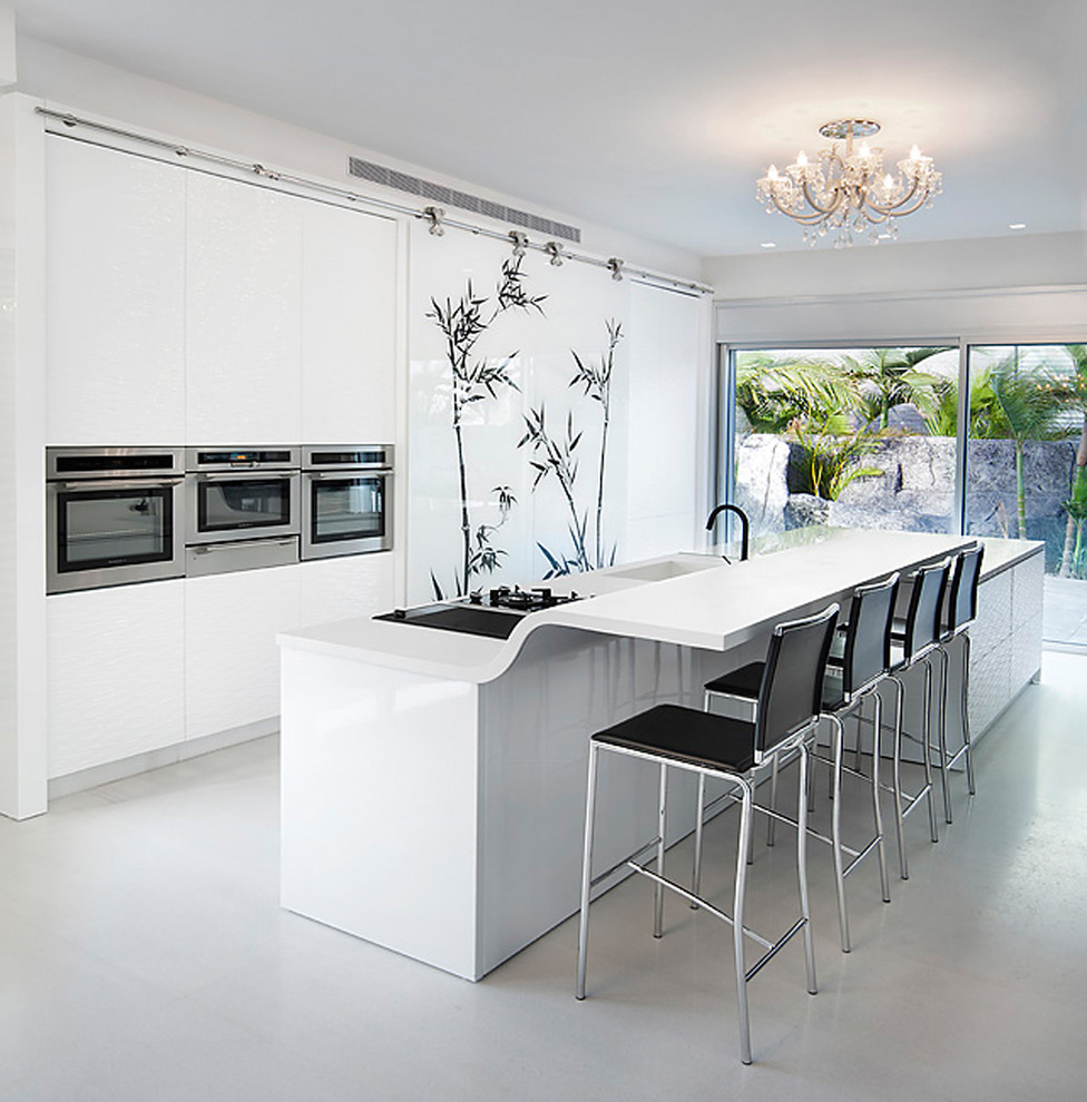 Trendy galley kitchen photo in Other with stainless steel appliances, an integrated sink, white cabinets and solid surface countertops