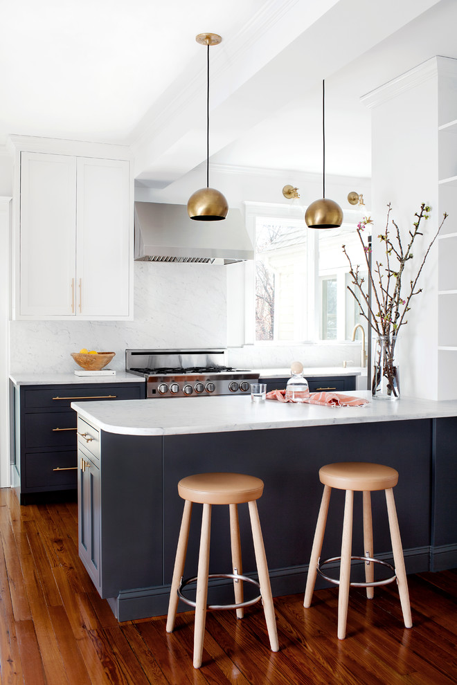 Transitional medium tone wood floor kitchen photo in Baltimore with shaker cabinets, marble countertops, stone slab backsplash, stainless steel appliances and a peninsula