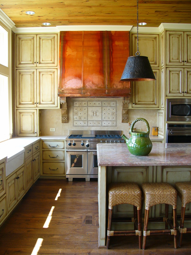 Elegant kitchen photo in Birmingham with stainless steel appliances, a farmhouse sink, raised-panel cabinets, distressed cabinets, marble countertops and beige backsplash