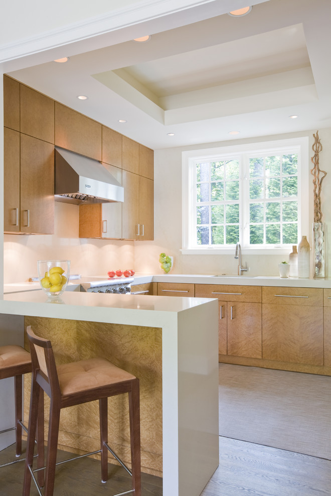 Example of a trendy u-shaped eat-in kitchen design in DC Metro with flat-panel cabinets, light wood cabinets, an undermount sink, quartz countertops, beige backsplash, stone slab backsplash and stainless steel appliances